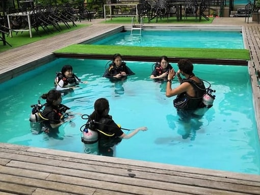 Instructor Joel briefing Open Water Diver students about pool exercises